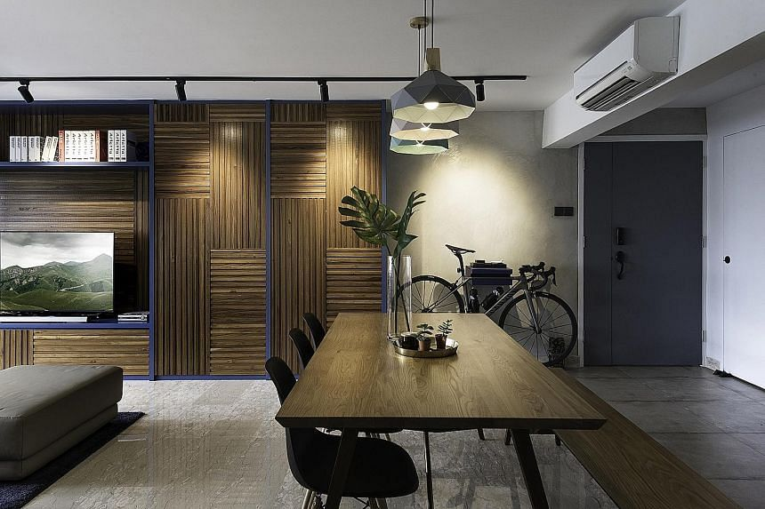 Teak pieces combine with Scandinavian blue laminate to create a feature wall in the living room (above); a cement wall acts as a subtle divider between the entrance foyer and the living space (left); and geometric-patterned tiles add whimsy to the ki