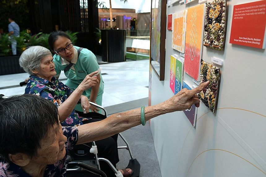 Madam Kwan Ah Geok (foreground), 91, and Madam Joan Oliviero, 82, from Econ Healthcare looking at artworks by other nursing home residents.