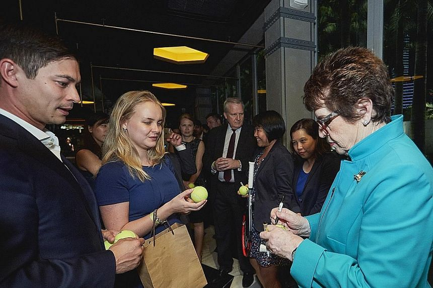 Ian Pryor, managing partner at IPP Financial Advisers, a returning customer of the Racquet Club - the WTA Finals hospitality programme - looking on as Billie Jean King signs tennis balls for guests on Thursday. They were at Marina Bay Sands where eve