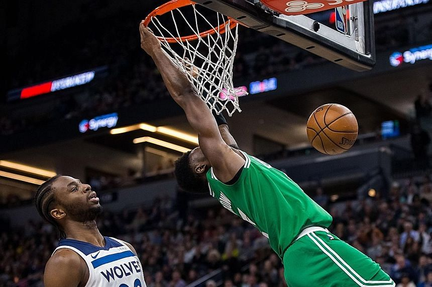 Boston Celtics guard Jaylen Brown dunking in the third quarter as Minnesota Timberwolves guard Andrew Wiggins looks on. Brown fell heavily on his back and head after this dunk, silencing the crowd, only to receive a standing ovation when he eventuall