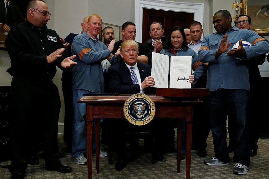 US President Donald Trump, flanked by steel and aluminium workers, at a signing ceremony at the White House in Washington on Thursday to establish tariffs on imports of steel and aluminium. The tariffs go into effect on March 23.