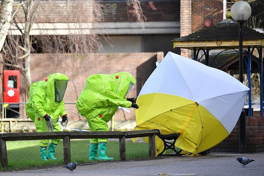 Emergency service officers in hazard suits fixing a tent over the bench where double agent Sergei Skripal and his daughter Yulia were found poisoned on Sunday. British detectives were scrambling to find the source of the nerve agent used.