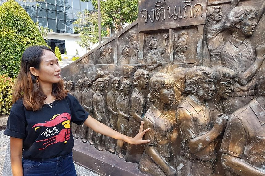 Ms Chonthicha Jangrew, who fronts the Democracy Restoration Group, stands by a pro-democracy sculpture in Thammasat University in Bangkok.