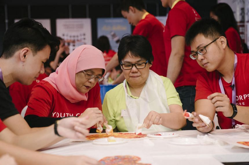 President Halimah Yacob (left) interacts with a person with special needs as part of a Youth Corps volunteer project.