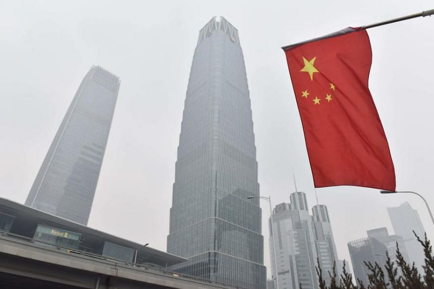 A Chinese flag flies near buildings in the central business district on a polluted day in Beijing on Feb 27, 2018.