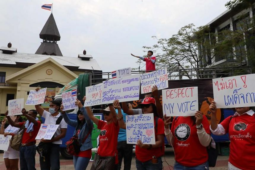 Thai anti-junta activists display placards during a pro-democracy rally at a university field in Bangkok on March 10, 2018.