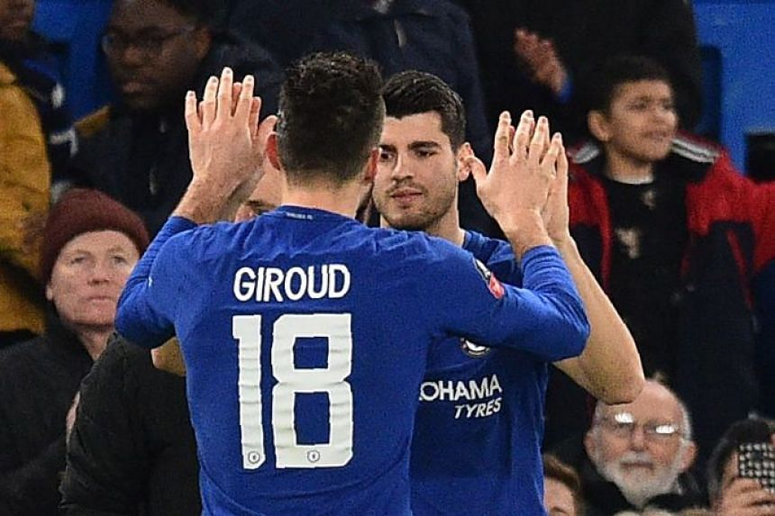 Morata (right) greeting team mate Giroud during a substitution.