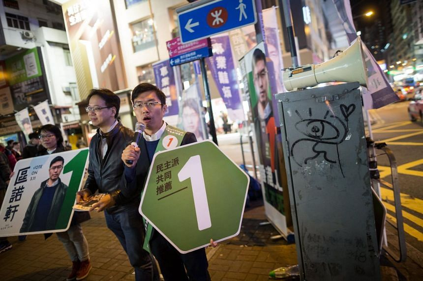 Pro-democracy Legislative Council by-election candidate Au Nok-hin (right) canvasses for votes in Wanchai, Hong Kong, on March 9, 2018.