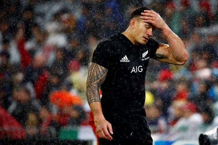 The officials posed with spectators wearing masks showing the face of All Black rugby player Sonny Bill Williams (above).