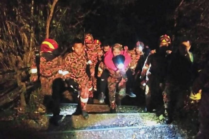 Firemen carrying a woman suffering from severe mountain sickness back to base at Mount Kinabalu.