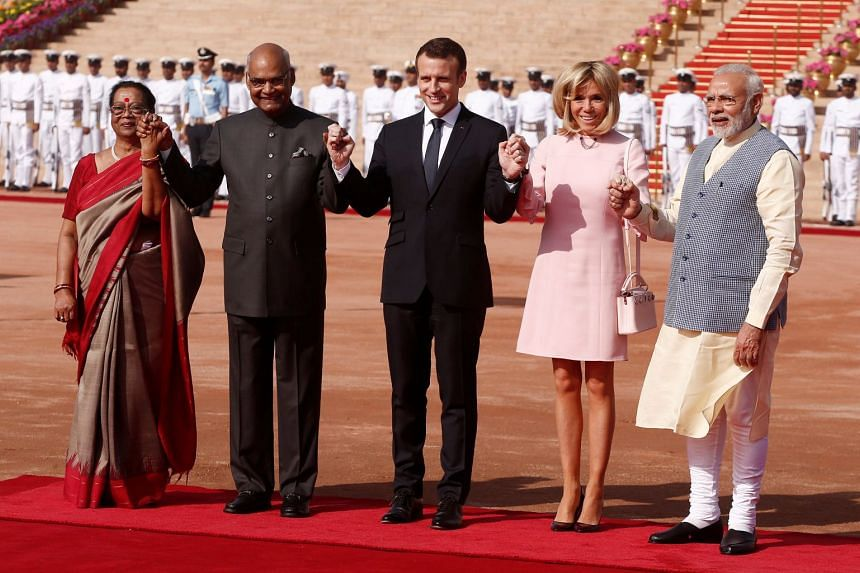 French President Emmanuel Macron (centre) his wife Brigitte Macron (second from right) India's President Ramnath Kovind (second from left) his wife Savita Kovind (left) and India's Prime Minister Narendra Modi hold hands during Macron's ceremonial