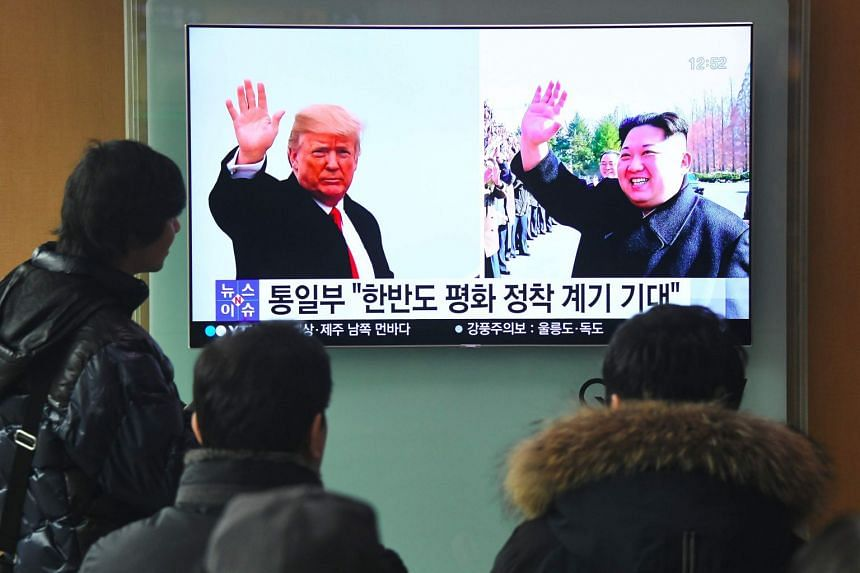 People watching a television news report showing pictures of US President Donald Trump (left) and North Korean leader Kim Jong Un at a railway station in Seoul on March 9, 2018.