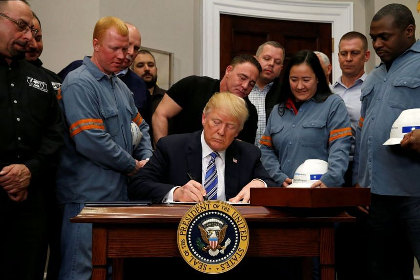 US President Donald Trump signing a presidential proclamation placing tariffs on steel and aluminum imports while surrounded by workers at the White House in Washington, DC, on March 8, 2018.