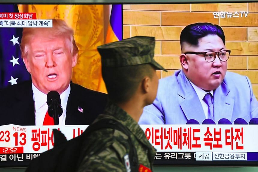 A South Korean soldier walks past a TV screen showing pictures of  Trump (left) and Kim in Seoul on March 9, 2018.
