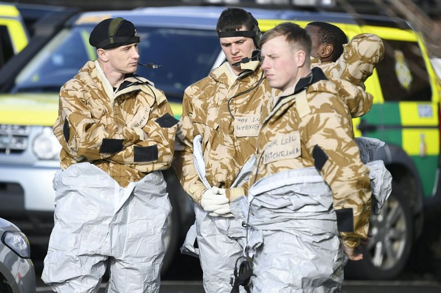 Members of the armed forces in protective suits prepare to remove an ambulance in Salisbury, Britain.
