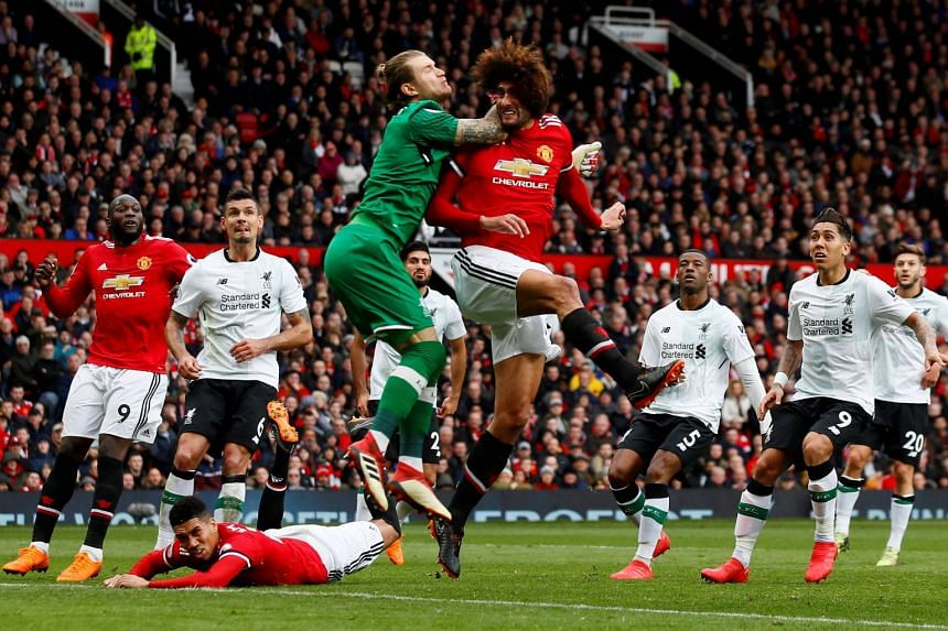 Liverpool's Loris Karius punches the ball clear from Manchester United's Marouane Fellaini.