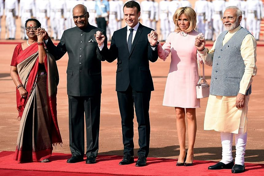 (From left) Mrs Savita Kovind, her husband and Indian President Ram Nath Kovind, French President Emmanuel Macron, his wife Brigitte and Indian Prime Minister Narendra Modi at a ceremonial reception at the Indian Presidential Palace in New Delhi yest