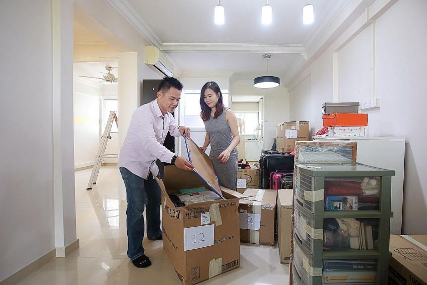 Above: Mr Leon Chea and his wife Mandy Chan unpacking their belongings in their new resale HDB flat in Hougang. Left: Mr Chea and Ms Chan with sellers, businessman Choo Choon Hock and his wife Lee Ai Wah.