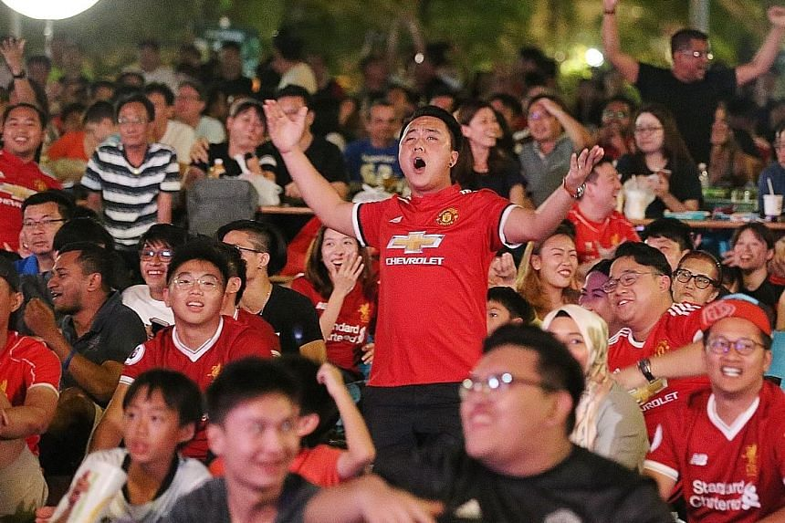 Manchester United supporters cheering after their team opened the scoring against Liverpool last night. Close to 1,000 people gathered to catch the live telecast at the lawn in front of Victoria Memorial Hall.