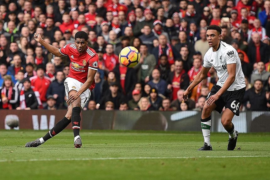 Manchester United's English striker Marcus Rashford scoring the opening goal against Liverpool, with defender Trent Alexander-Arnold powerless to stop him, in their English Premier League match at Old Trafford. United's 2-1 win boosts their chances o