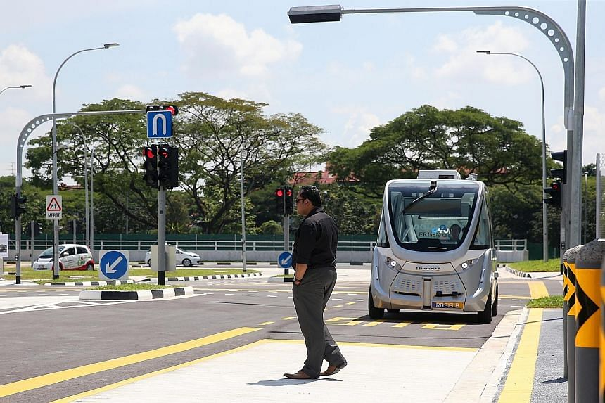 """A """"jaywalker"""" passing in front of a self-driving shuttle bus at an autonomous vehicle test centre in Singapore. It bothers the writer that humans are allowing programmed computers to operate cars - dangerous machines in themselves - with insufficient"""
