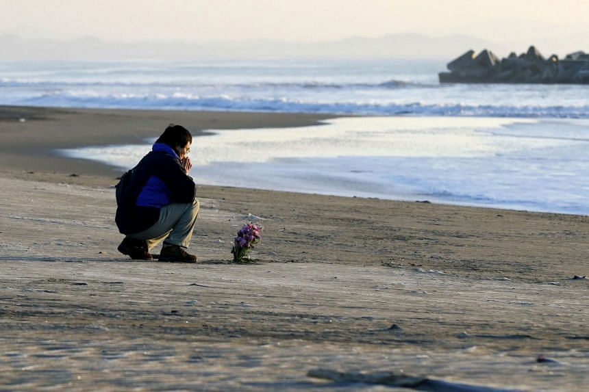 A man offering prayers at a beach in Arahama district, in Sendai, Miyagi prefecture, on March 11, 2018, to mark the 7th anniversary of the 2011 Tohoku earthquake.