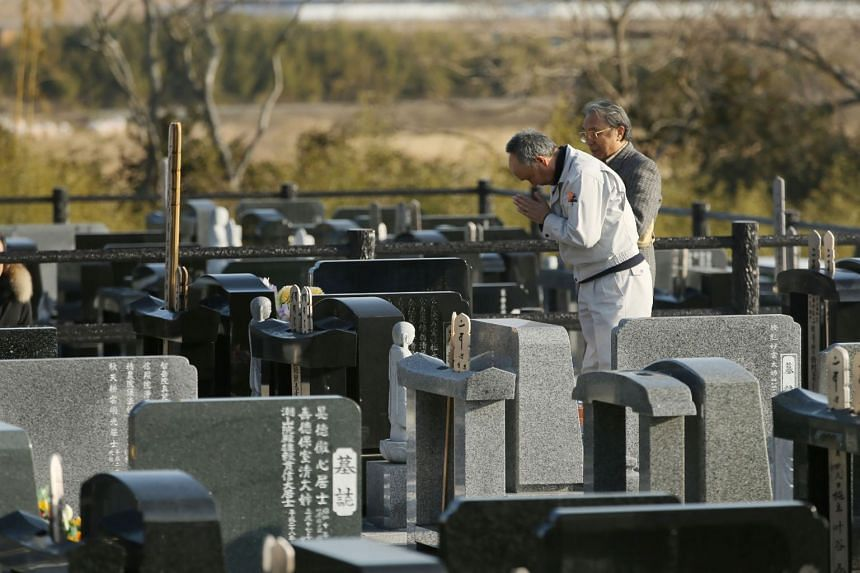 Relatives praying for the victims of the 2011 Great East Japan Earthquake, on the 7th anniversary of the disaster, in Namie, Fukushima prefecture, on March 11, 2018.