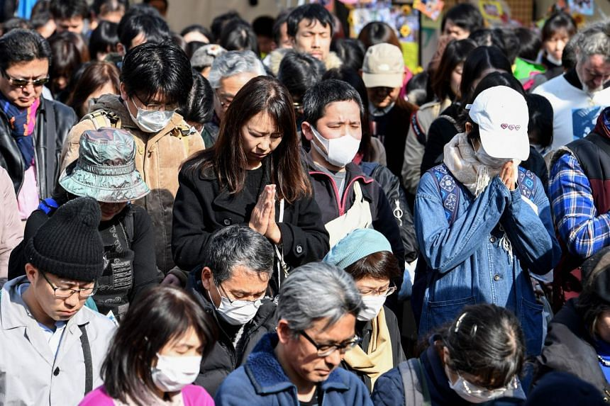 People marking a minute of silence for victims of the 2011 tsunami and earthquake disaster at a park in Tokyo on March 11, 2018.