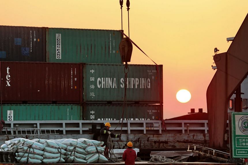 Workers loading ships at a port in Nantong, China, on March 9, 2018.