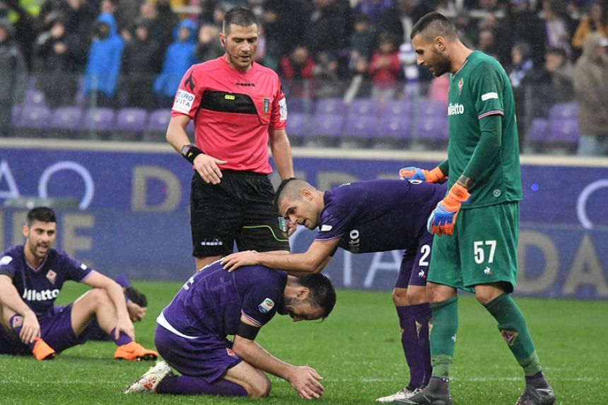 Fiorentina's new captain Milan Badelj is comforted by referee Fabrizio Pasqua and Fiorentina's Vincent Laurini at the end of the match.