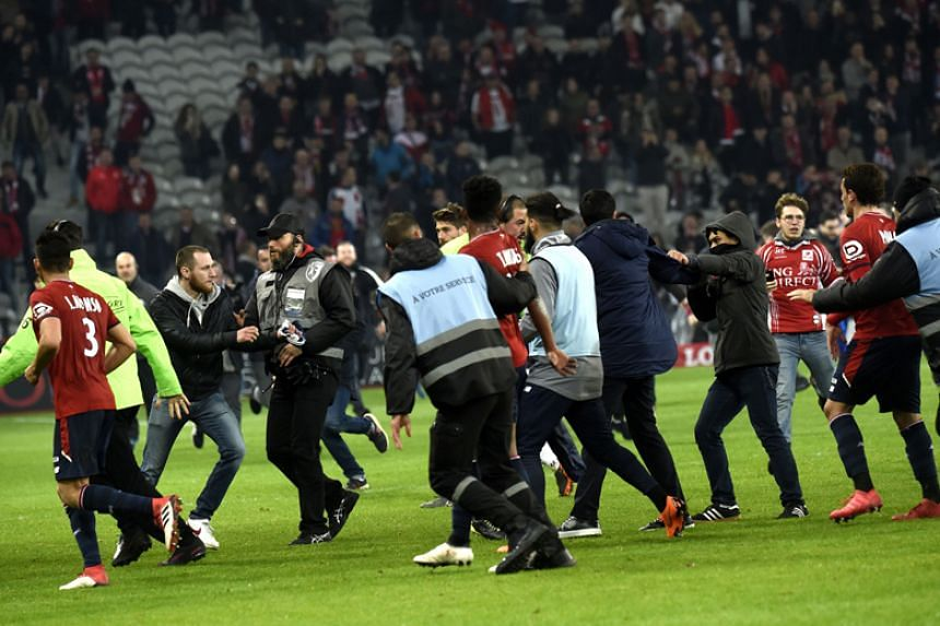 Lille supporters invade the pitch following the club's 1-1 draw with Montpellier at the Pierre-Mauroy stadium on March 10, 2018.