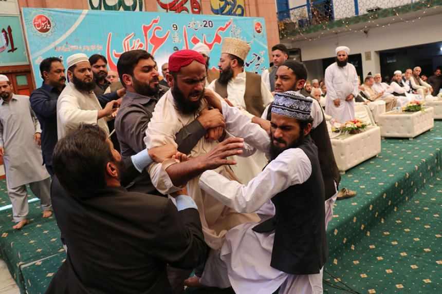 Security personnel hold a student after he hurled a shoe at former Pakistani Prime Minister Nawaz Sharif during a seminary in Lahore on March 11, 2018.