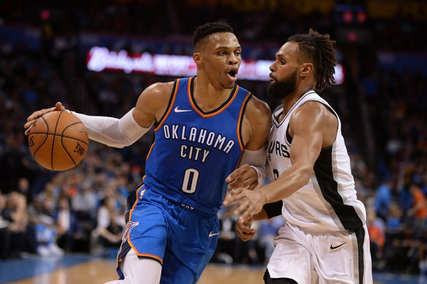 Oklahoma City Thunder guard Russell Westbrook drives to the basket in front of San Antonio Spurs guard Patty Mills during the second quarter their NBA match at Chesapeake Energy Arena in Oklahoma City on March 10, 2018.