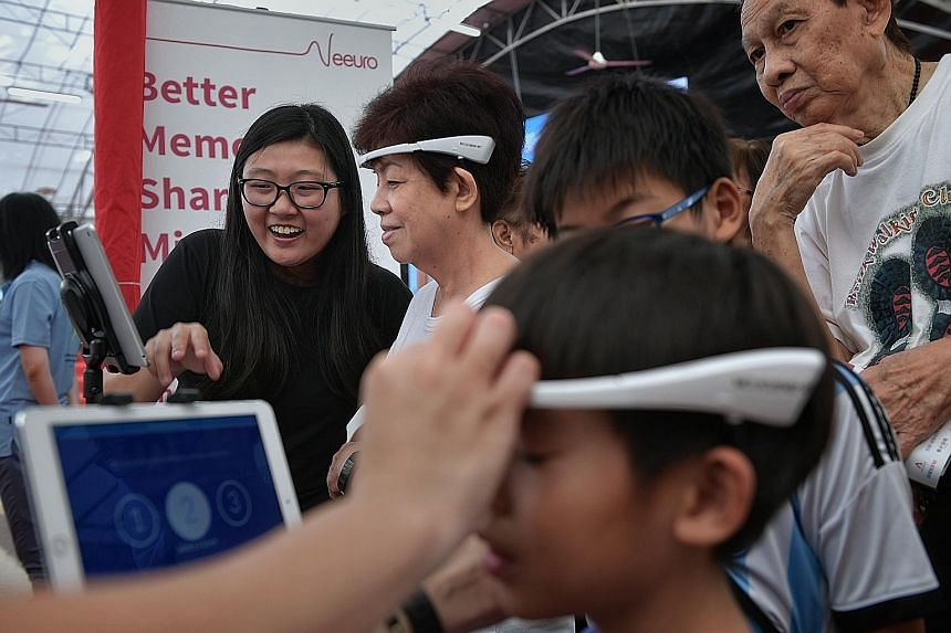 At the launch of the Digital Volunteers initiative yesterday was resident Chew Li Fong (second from left), 66, who wore a SenzeBand which detects brainwaves, as she played mental games on a tablet device.