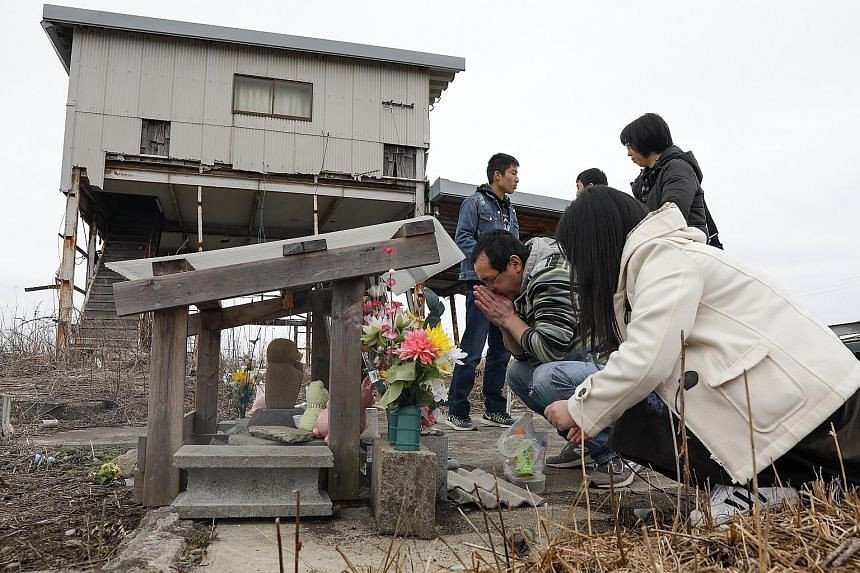 Family members who lost their loved ones during the Fukushima disaster offering prayers yesterday. More than 73,000 people are still displaced as a result of the disaster that hit Japan's north-eastern coast on March 11, 2011.