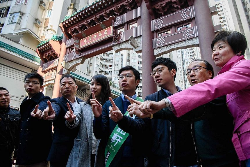 Pro-democracy campaigners Joshua Wong (left), Agnes Chow (third from left) and Nathan Law (fifth from left) lending support to pro-democracy candidate Au Nok Hin (with green sash) yesterday in Hong Kong's Legislative Council by-elections, which have