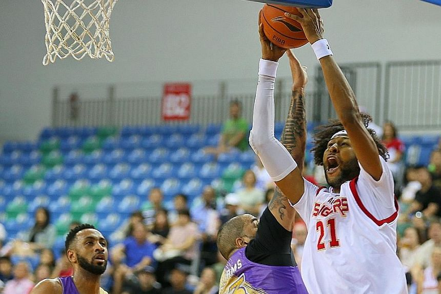 Singapore Slingers centre Christien Charles driving past the CLS Knights' Brian Williams as Shane Edwards looks on. Charles scored 16 points in the upset defeat.