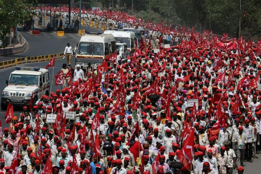 Farmers from Nashik, situated 165 kilometres north of India's financial capital, walk on the roadside towards Mumbai, as they organised a protest rally on March 11, 2018.