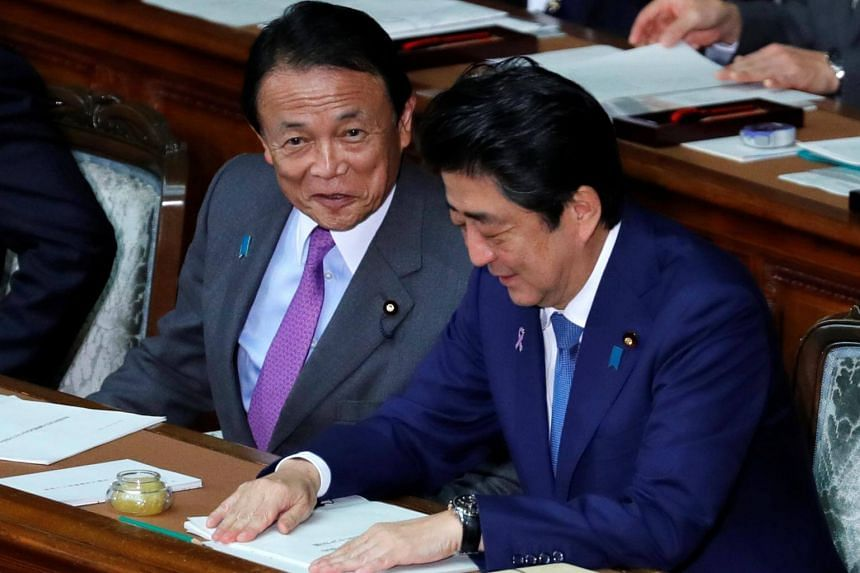 Japan's Prime Minister Shinzo Abe (right) talks with Deputy Prime Minister and Finance Minister Taro Aso at the lower house of parliament in Tokyo, on Nov 17, 2017.