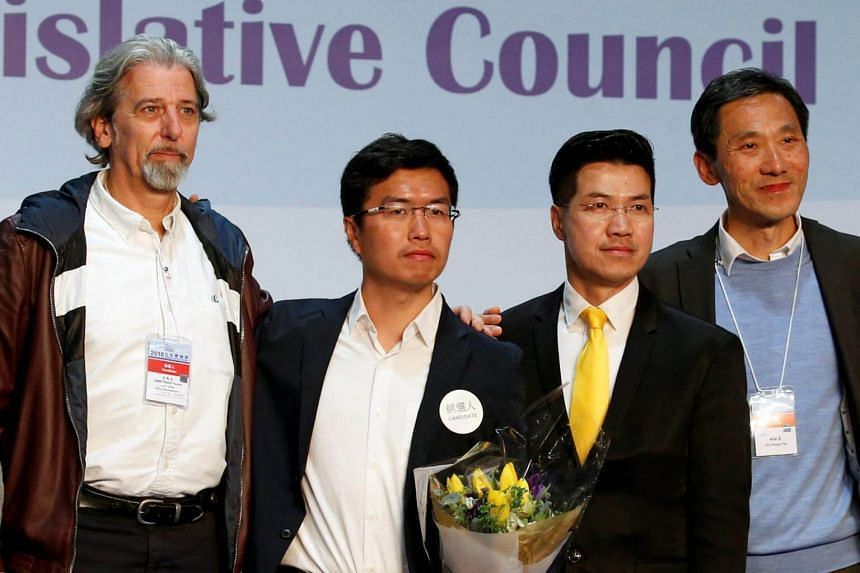 Pro-democracy candidates (from left) Paul Zimmerman, Au Nok-hin, Gary Fan and Edward Yiu pose on the podium after the Legislative Council by-election in Hong Kong.