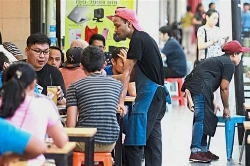 Workers serving customers at an eatery in Petaling Jaya, Malaysia.