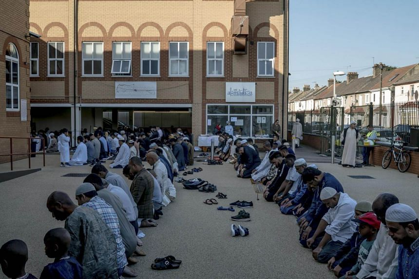 Muslims pray outside a mosque in Barking, England.