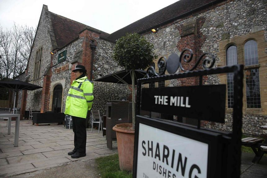 A police officer stands in front of The Mill pub in Salisbury, England, on March 11, 2018, as investigations continue in connection with the nerve agent attack a week ago.