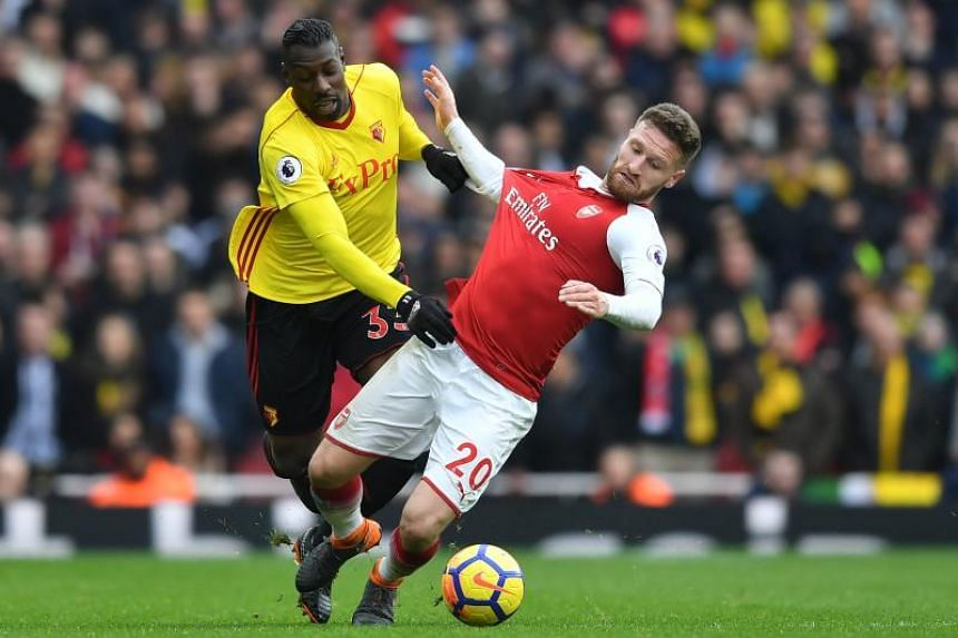 Watford's Italian striker Stefano Okaka (left) vies with Arsenal's German defender Shkodran Mustafi during the English Premier League football match between Arsenal and Watford at the Emirates Stadium in London on March 11, 2018.