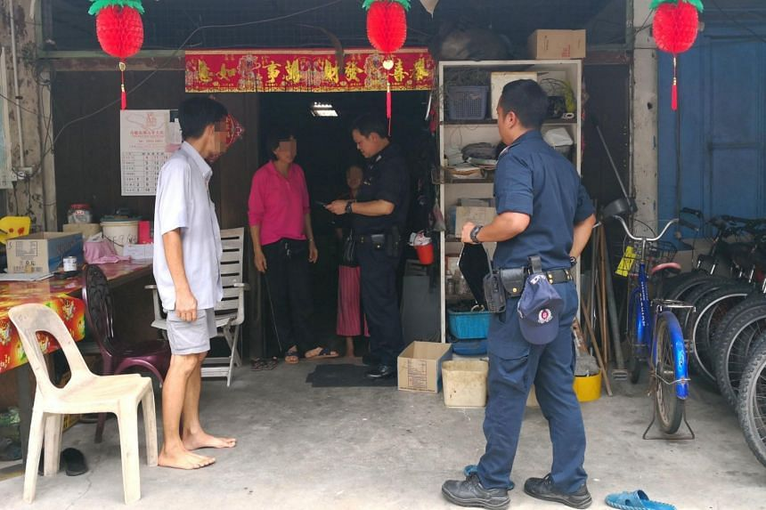 Police officers hold up a photo while searching for the man in Pulau Ubin on March 12, 2018.