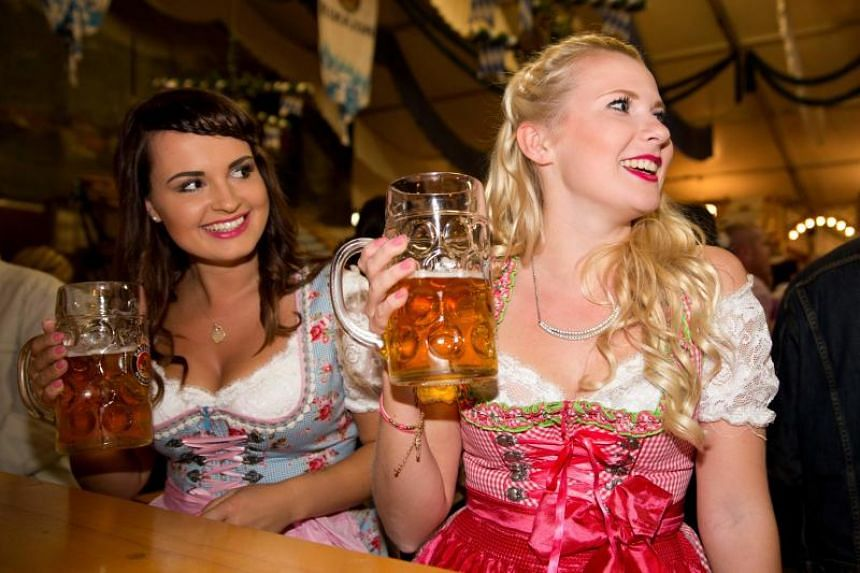This file photo taken on Oct 8, 2015, shows women in traditional Dirndl dresses holding a stein of beer as they attend the opening of the Oktoberfest beer festival in Paris.