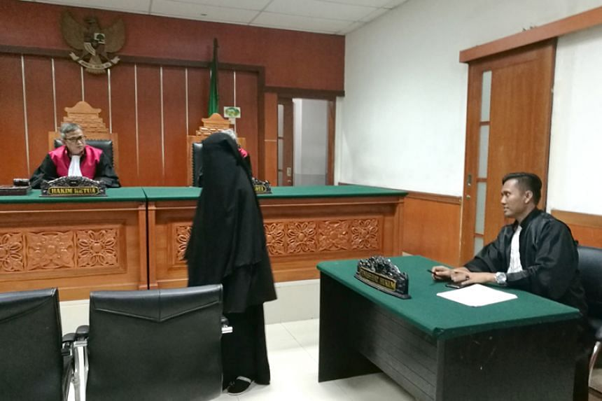 Former Indonesian migrant worker Anggi Indah Kusuma (centre) is now facing the death sentence along with her husband for planning terror attacks and making explosives in a rented house in Bandung.