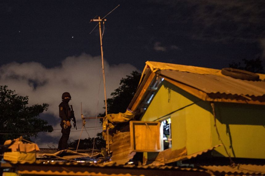 A policeman keeps watch from a rooftop during a drug raid in Maharlika Village, Taguig, Manila, on Feb 28, 2018.