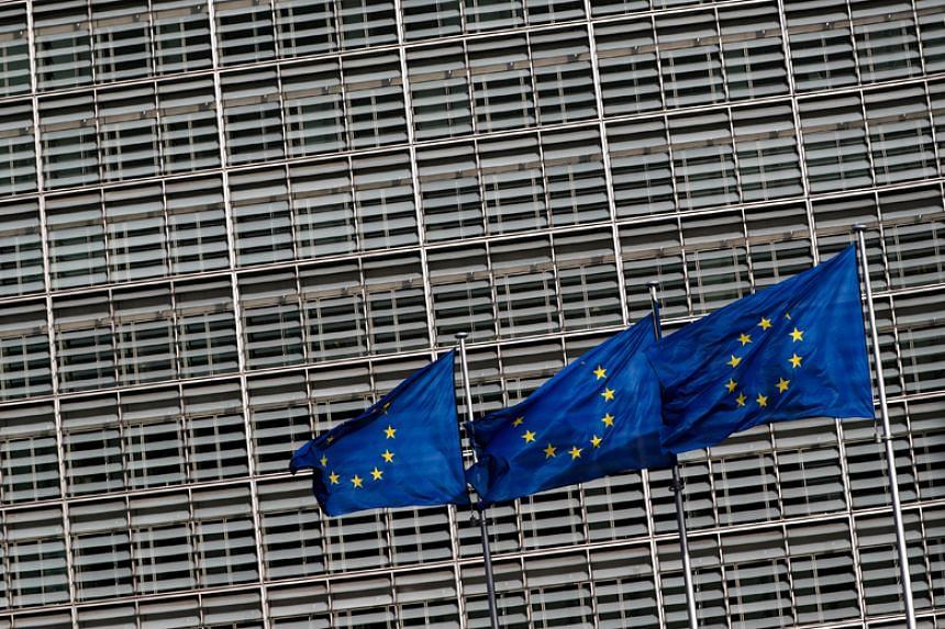 European Union flags outside the EU Commission headquarters in Brussels. A report by the EU's executive arm is warning against simplistic solutions to the problems of disinformation.