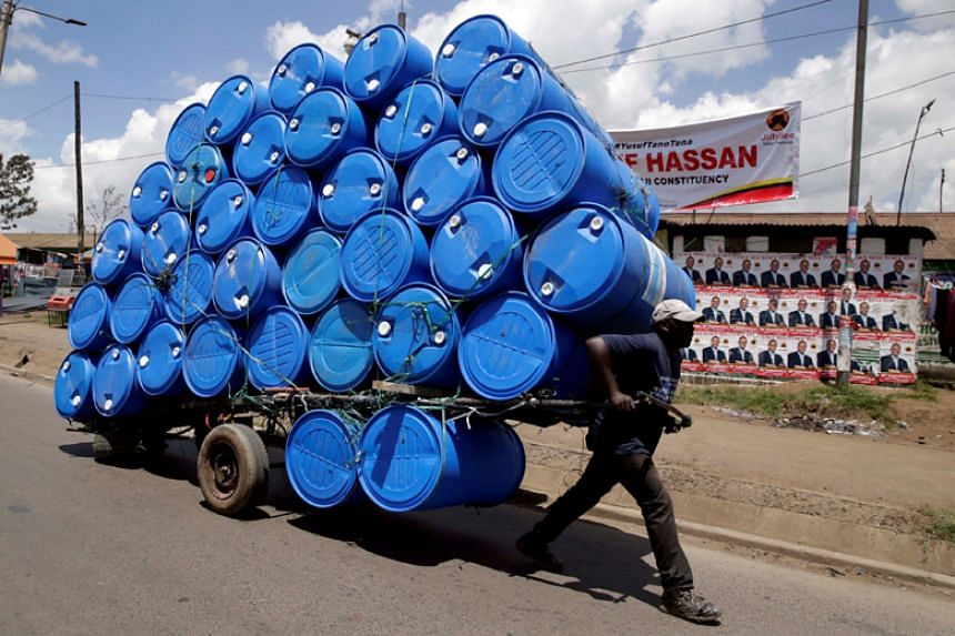 A porter transports a cart loaded with empty plastic drums to a recycling dealer in the outskirts Nairobi on April 26, 2017.